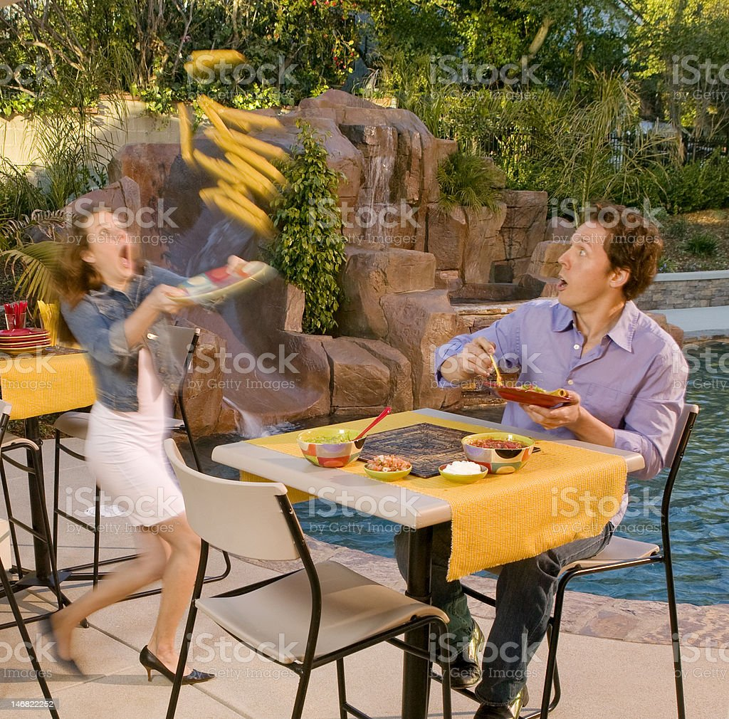 Woman spilling food by poolside table with man royalty-free stock photo
