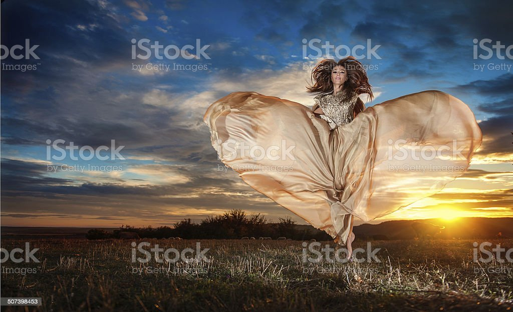 Woman spinning around looking as a butterfly in sunset stock photo