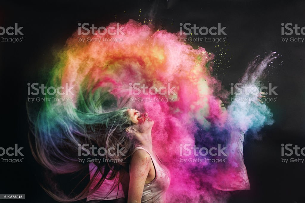Woman splashing hair with holi powder stock photo
