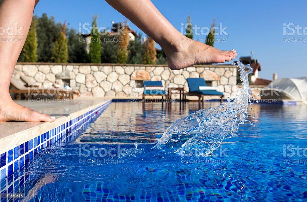 Woman splashing water in the pool stock photo