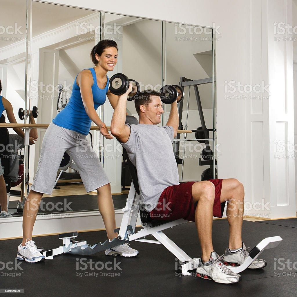 Woman spotting man at gym royalty-free stock photo