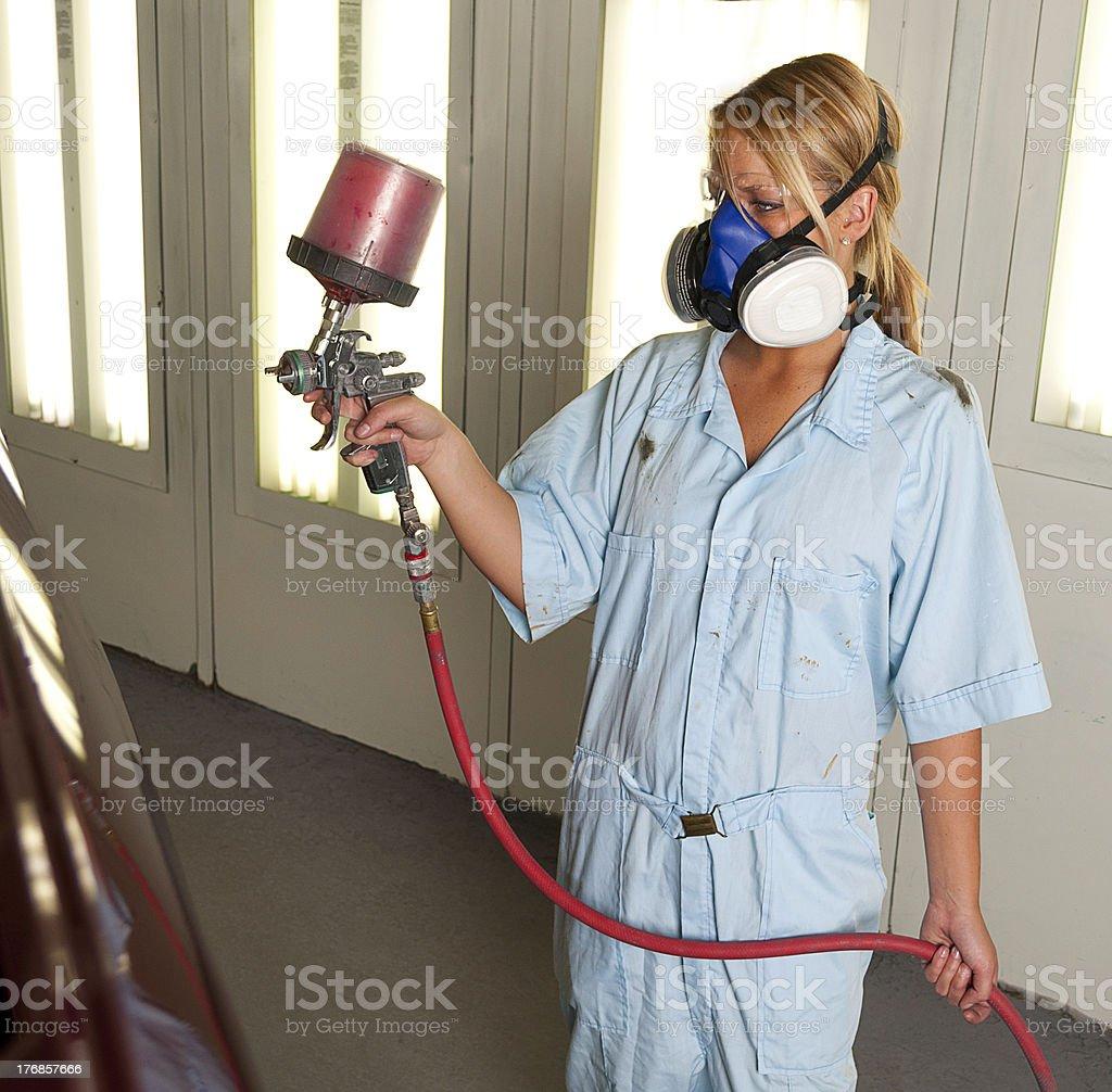 Woman spray painting vehical stock photo