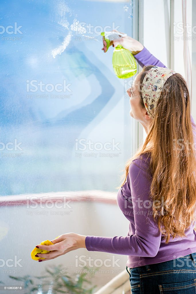 Woman Spraying Cleaning Fluid on Windows, Copy Space stock photo