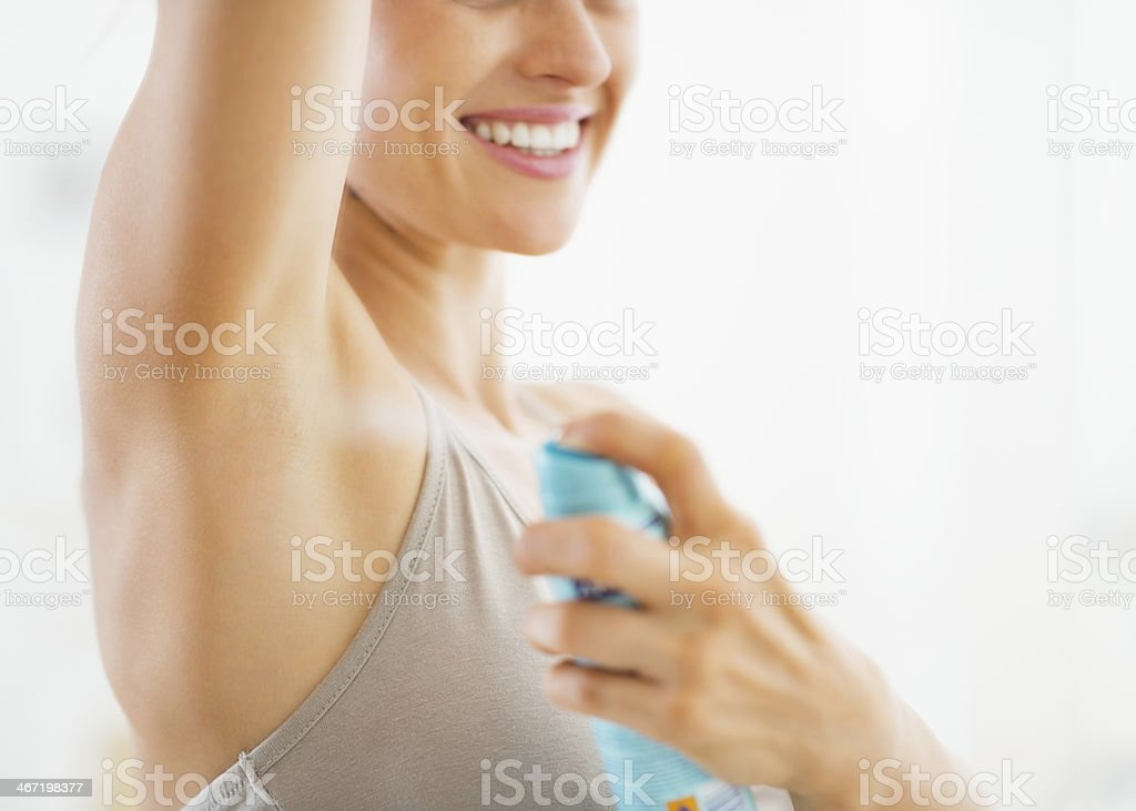 Woman spraying deodorant to her underarm stock photo
