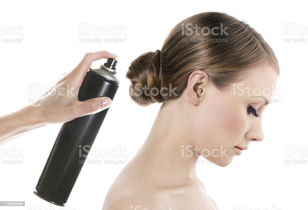 Woman spraying hairspray onto a woman's hair stock photo
