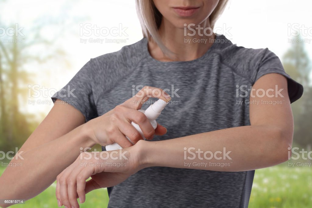 Woman spraying insect repellent on skin outdoor stock photo