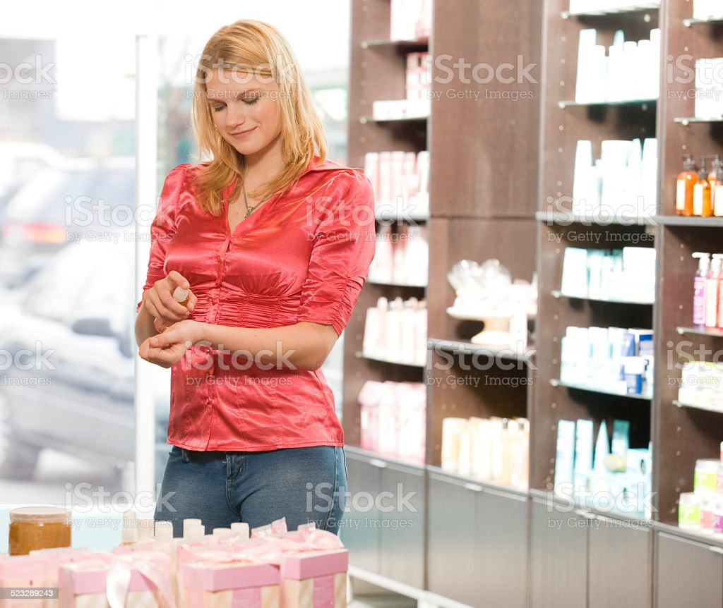 Woman Spraying Perfume in Retail Store stock photo