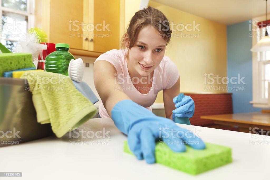 Woman Spring Cleaning Kitchen Counter with Cleanser and Sponge royalty-free stock photo