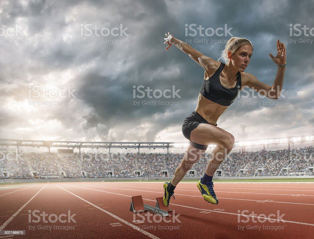 Woman Sprinter Explodes Out Of Blocks In Floodlit Athletics Arena stock photo