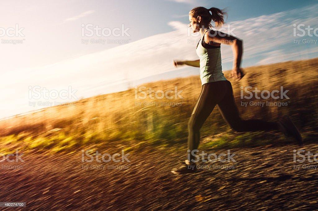 Woman Sprinting on Beautiful Sunset Road stock photo