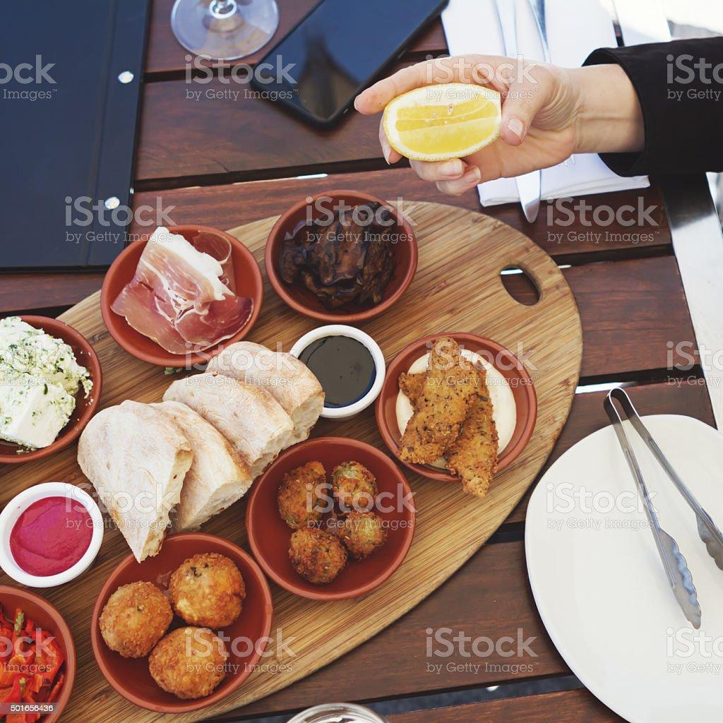 Woman squeezing lemon onto antipasto platter entree stock photo