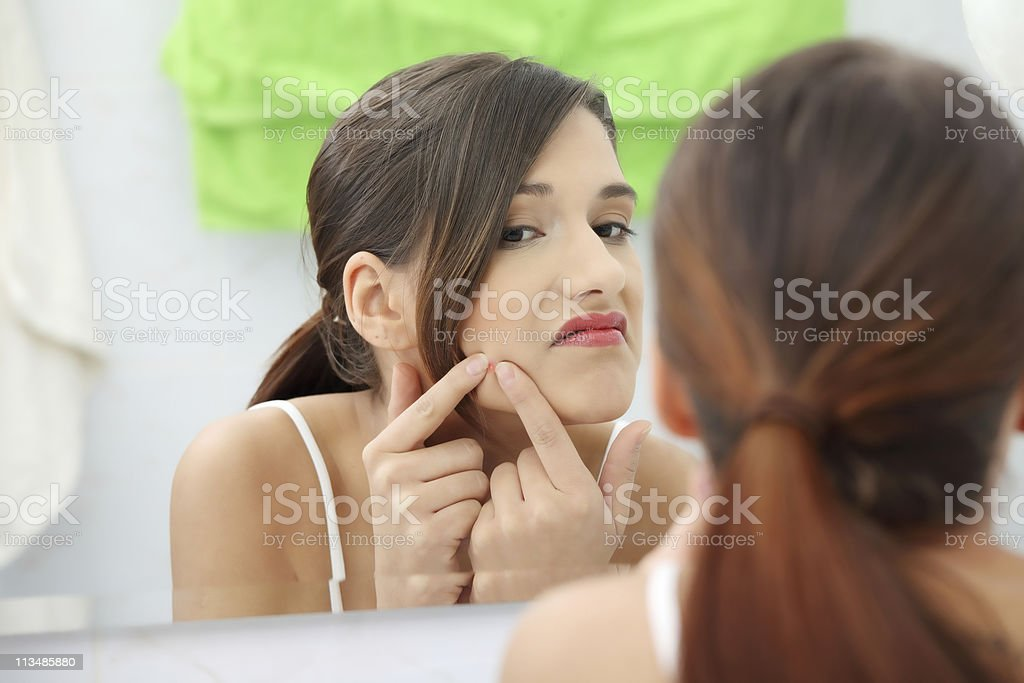 Woman squeezing pimple stock photo