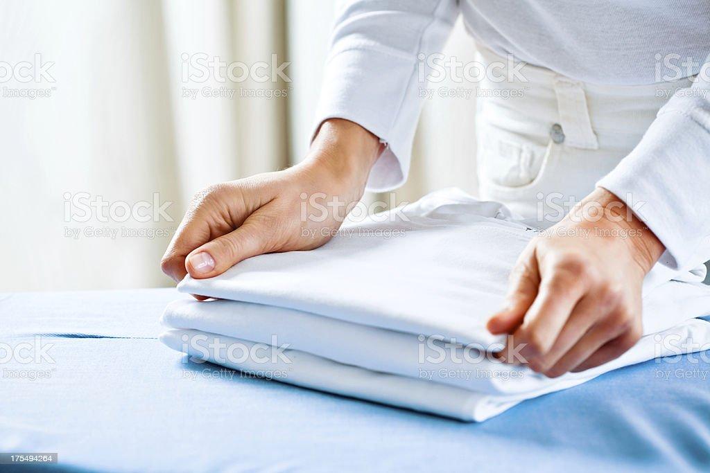 Woman Stacking Ironed Folded Shirts stock photo