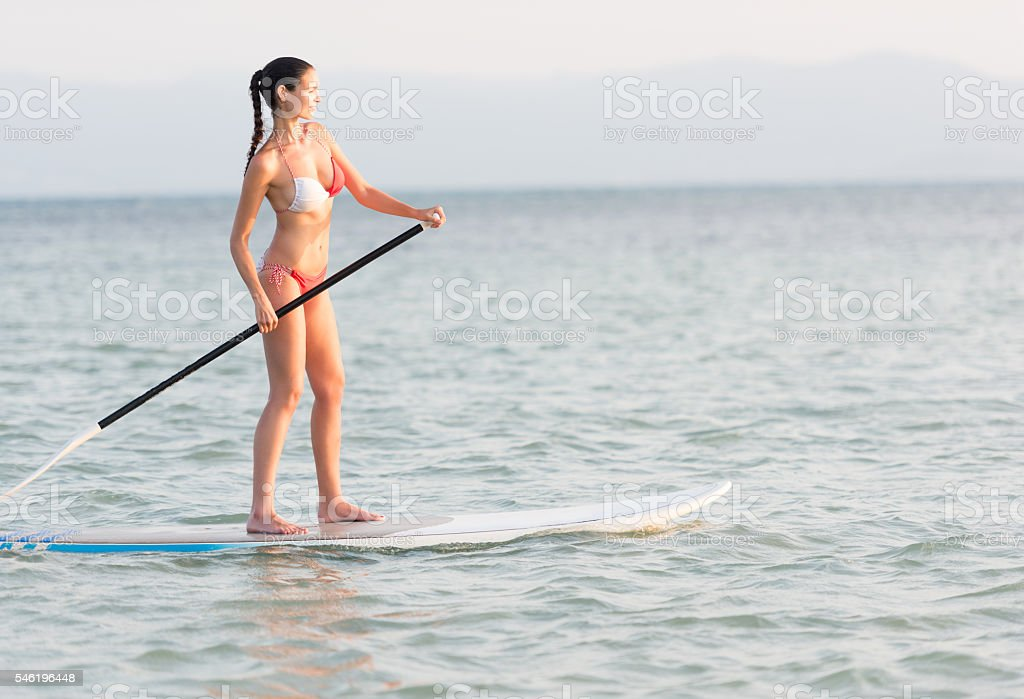 Woman Stand Up Paddling (SUP) at sunset stock photo