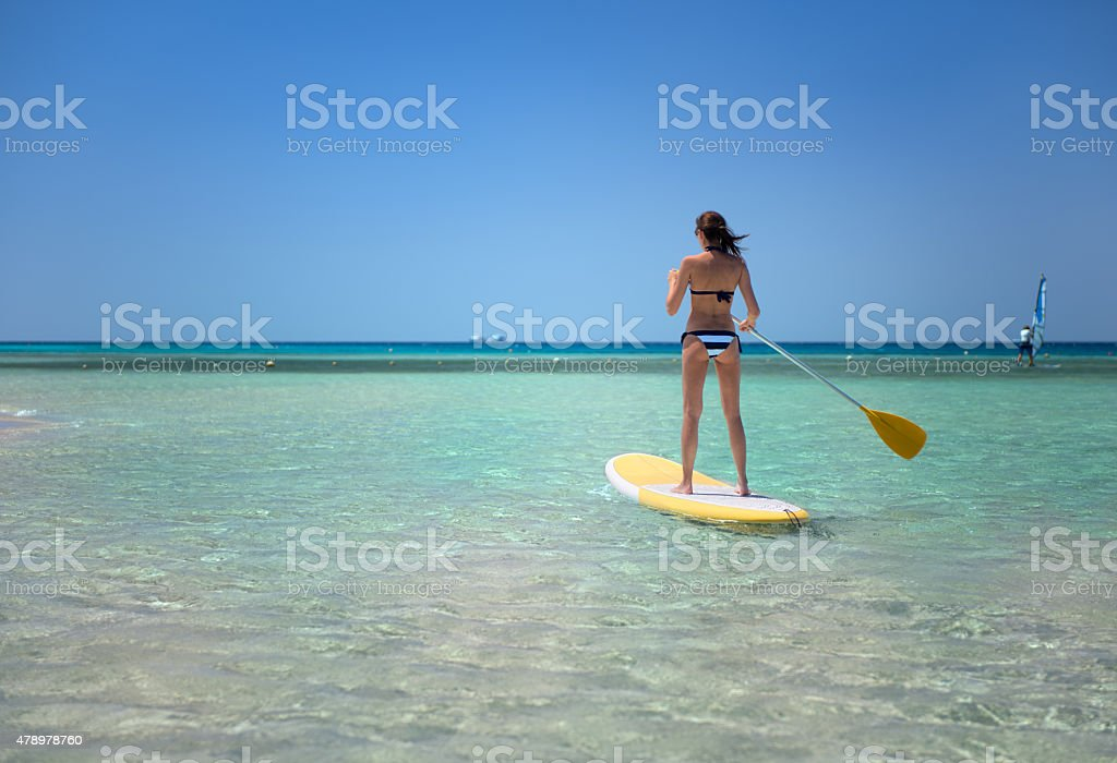 Woman Stand Up Paddling (SUP) stock photo