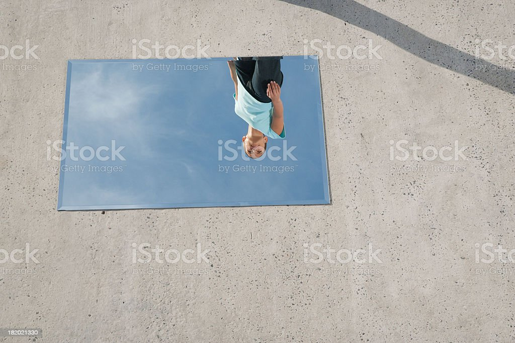 Woman standing above mirror and reflection outdoors stock photo