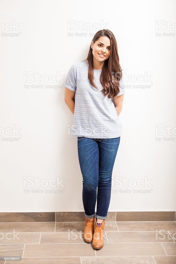 Woman standing against a white wall stock photo
