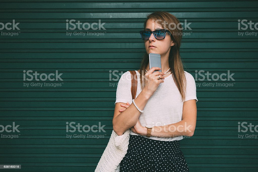 Woman standing against green wall stock photo