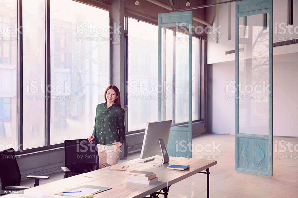 Woman standing alone in large modern bright design office stock photo