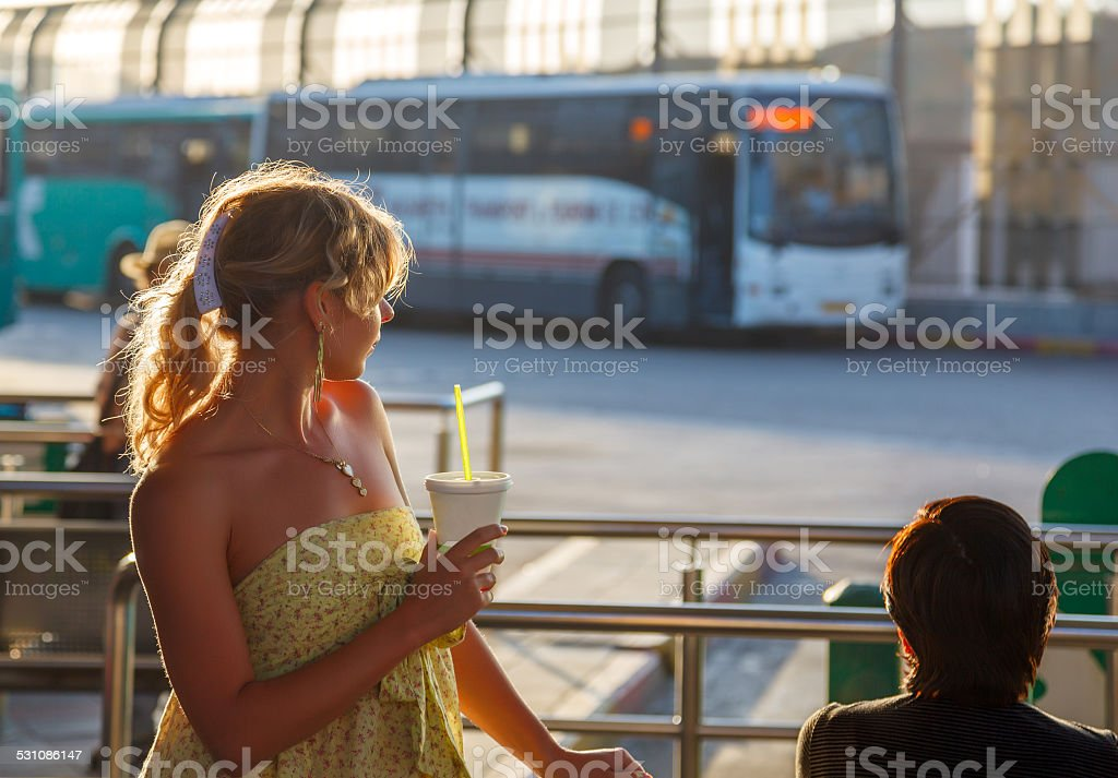 Woman standing at bus station stock photo