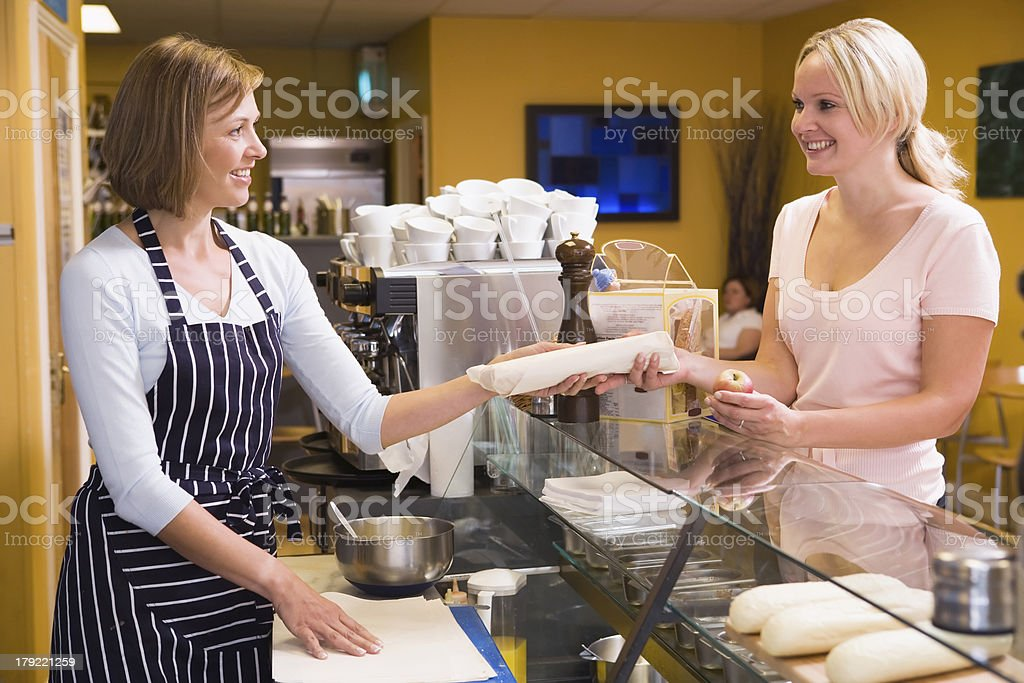 Woman standing at counter in restaurant serving customer and smiling stock photo