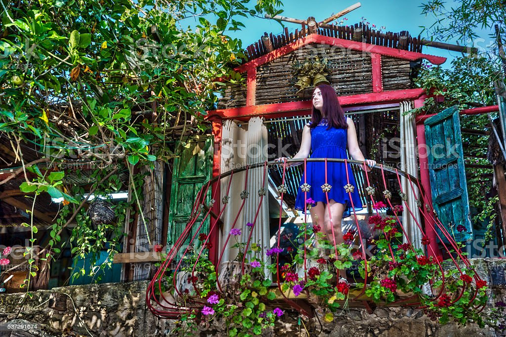 Woman standing at flowered balcony looking at the garden stock photo