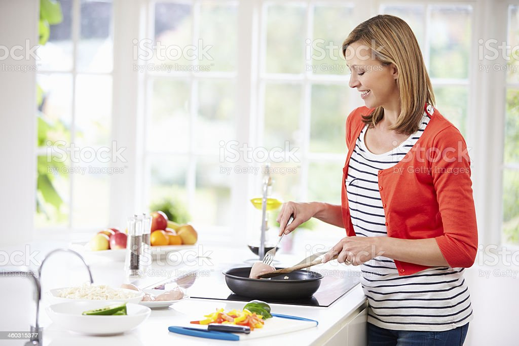Woman Standing At Hob Preparing Meal In Kitchen stock photo