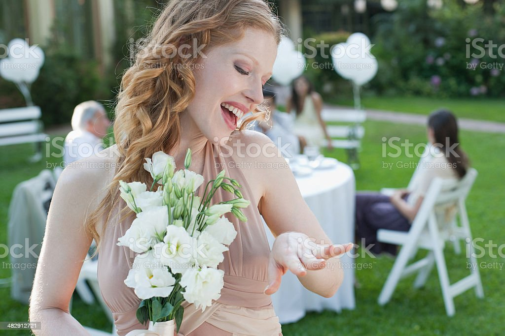 Woman standing at outdoor party with flowers showing off new ring smiling stock photo