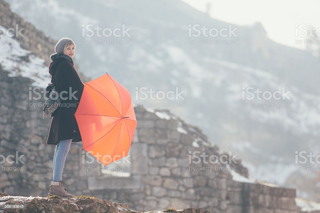Woman standing at the hill holding umbrella stock photo
