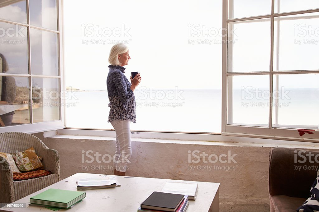 Woman Standing At Window And Looking At Beautiful Beach View stock photo