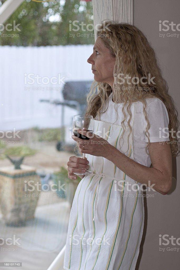 Woman standing at window drinking wine stock photo