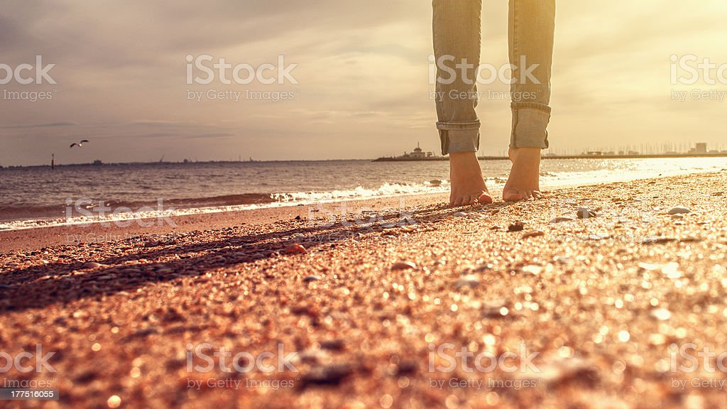 A woman standing barefoot on the beach stock photo
