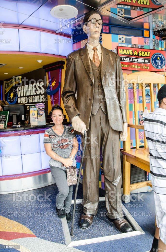 Woman standing besides a statue of Robert Wadlow, the tallest man ever stock photo