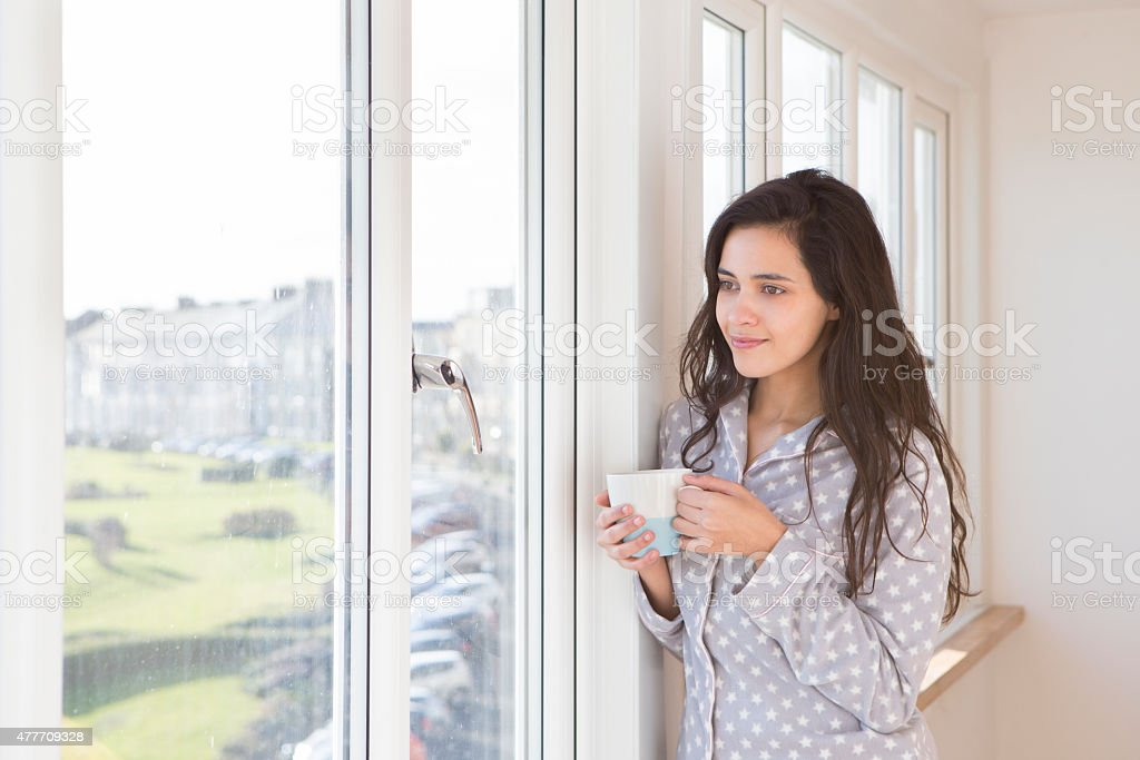Woman Standing by a Window Drinking Coffee in her Pyjamas stock photo