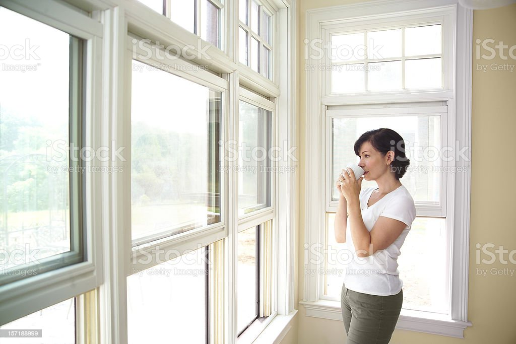 woman standing by a window drinking coffee stock photo