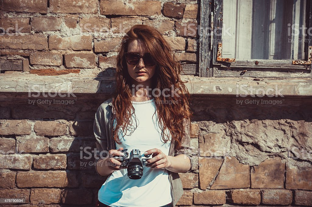 Woman standing by the wall and holding retro camera, stock photo