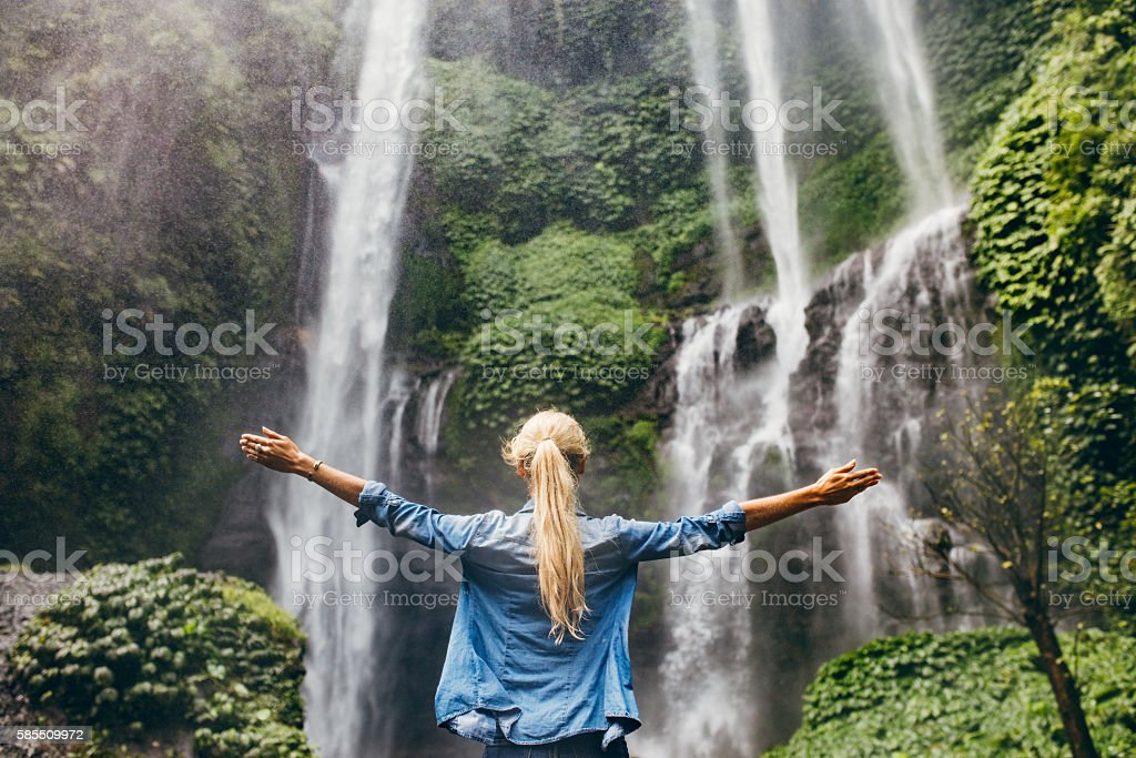 Woman standing by waterfall with her hands raised stock photo
