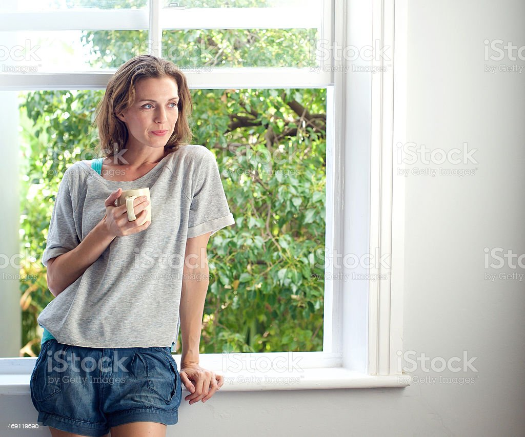 Woman standing by window at home with cup of coffee stock photo