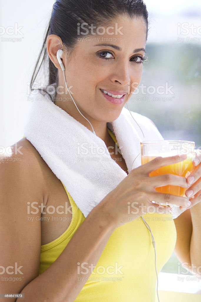 Woman standing holding glass of orange juice wearing headphones stock photo