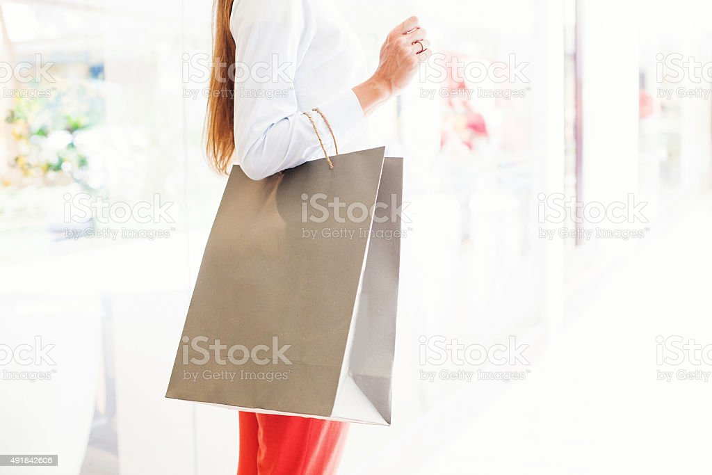 Woman standing in a street with paper bag stock photo