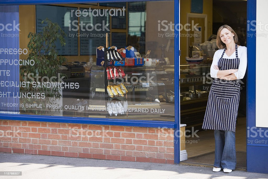 Woman standing in doorway of restaurant smiling stock photo