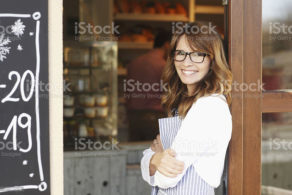 Woman standing in front of coffee shop stock photo