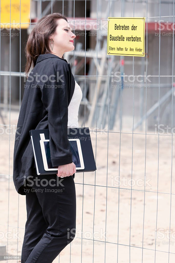woman standing in front of construction site holding a book stock photo
