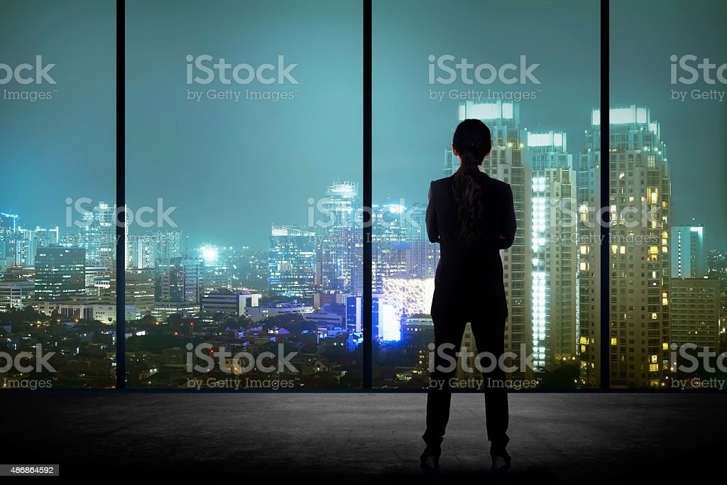 Woman standing in his office looking at the city stock photo