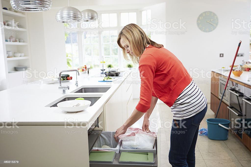 Woman Standing In Kitchen Emptying Waste Bin stock photo