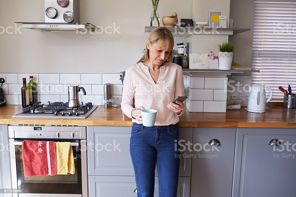 Woman Standing In Kitchen Sending Text Message On Phone stock photo