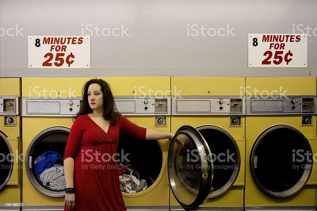 Woman Standing in Laundromat Near Washing Machines royalty-free stock photo