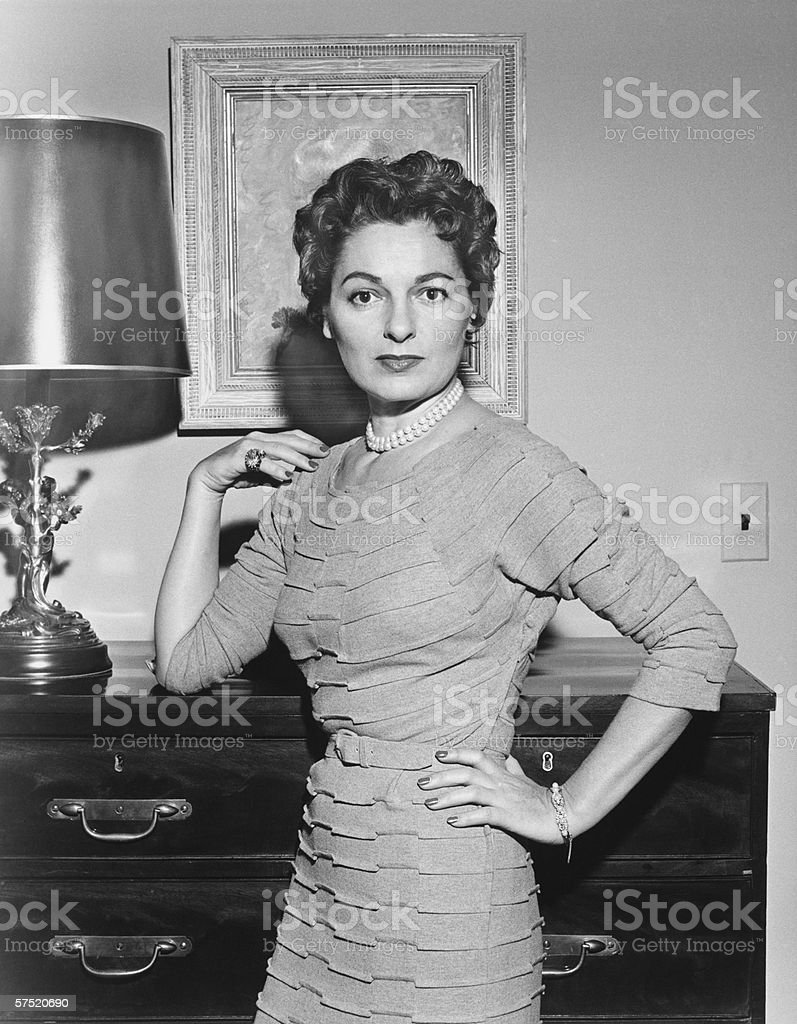 Woman standing in living room with hand on cabinet, (B&W) stock photo