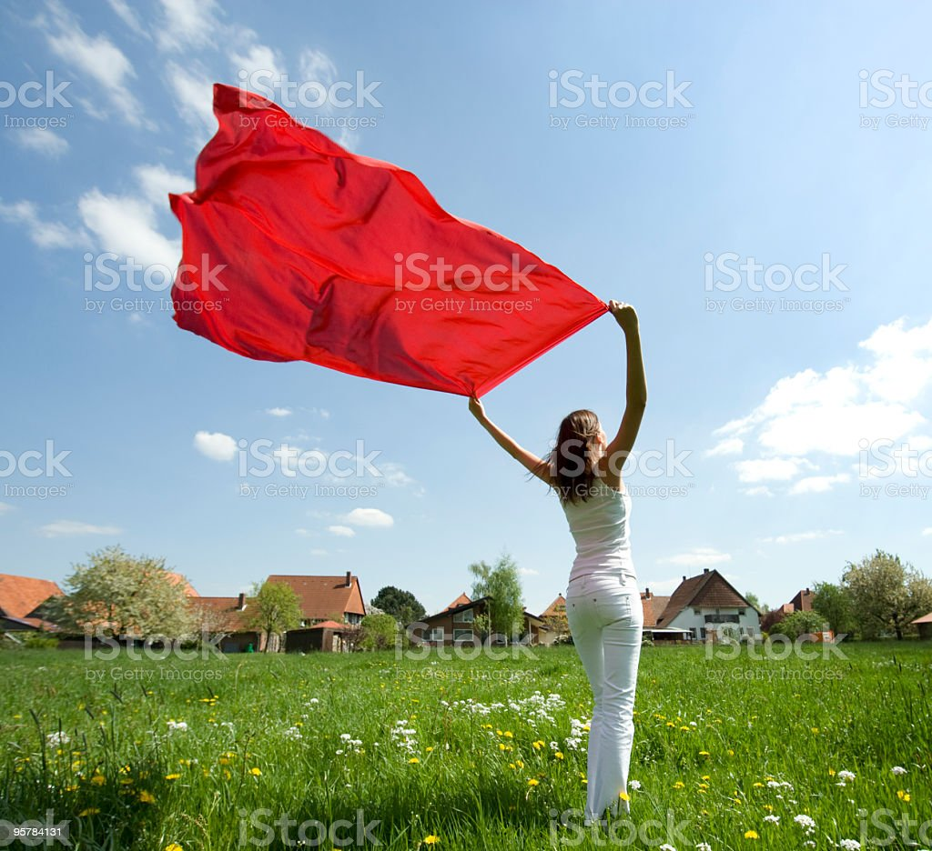 Woman Standing in Meadow Holding red scarf to Wind (XL) royalty-free stock photo