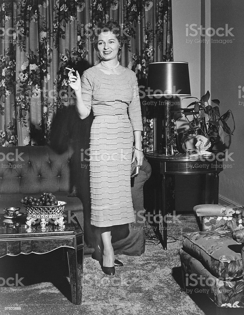 Woman standing in rich living room, holding cigarette, (B&W) stock photo